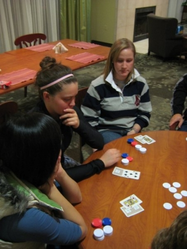 Katie is planning out her next move during an intense game of poker with the Hope Lodge residents.